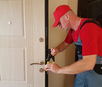 Мастер ремонтирует входную дверь